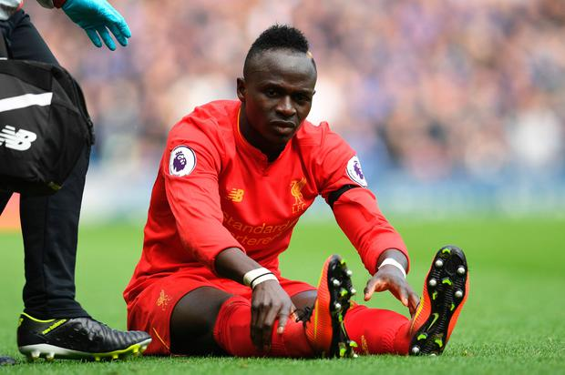 Liverpool's Senegalese midfielder Sadio Mane reacts after picking up an injury during the English Premier League football match between Liverpool and Everton at Anfield in Liverpool, north west England on April 1, 2017. AFP/Getty Images