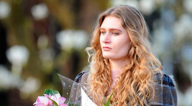 Lydia Wilkinson looks at the flowers laid in tribute to her brother and mother. Photo: Rui Vieira/PA Wire