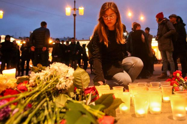 A woman lights a candle at an entrance to Sennaya subway station after an explosion in St.Petersburg subway in St.Petersburg, Russia, Monday, April 3, 2017. (AP Photo/Yevgeny Kurskov)