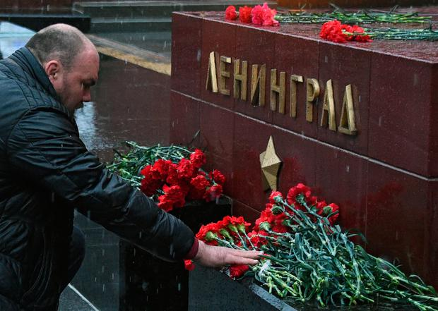 A man lays flowers in memory of victims of the blast in the Saint Petersburg metro at a memorial stone reading Leningrad by the Kremlin wall in central Moscow on April 3, 2017. AFP/Getty Images