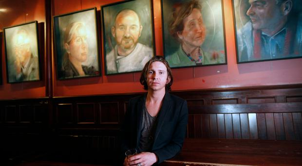 Artist Christopher James McGarry with his paintings on display at the John Hewitt pub in Belfast