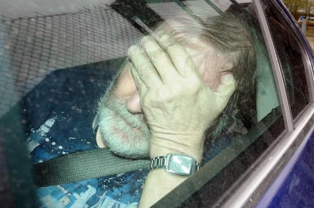 Keith Baker attempts to shield his face on his way to court