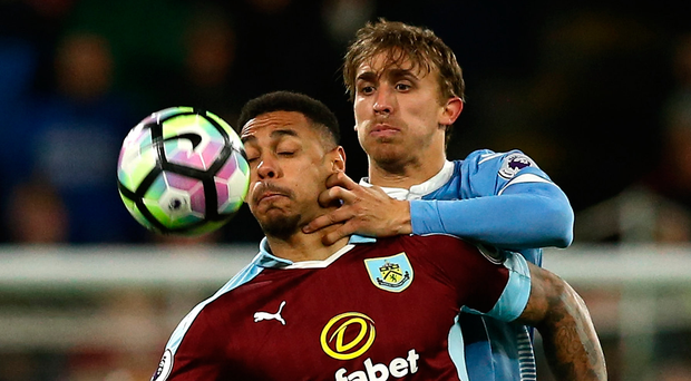 Andre Gray of Burnley (left) and Marc Muniesa of Stoke City battle for the ball during the Premier League match at Turf Moor