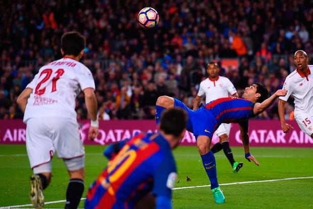 Barcelona's Uruguayan forward Luis Suarez (C) jumps to score during the Spanish league football match FC Barcelona vs Sevilla FC at the Camp Nou stadium in Barcelona on April 5, 2017. / AFP PHOTO / Josep LAGOJOSEP LAGO/AFP/Getty Images