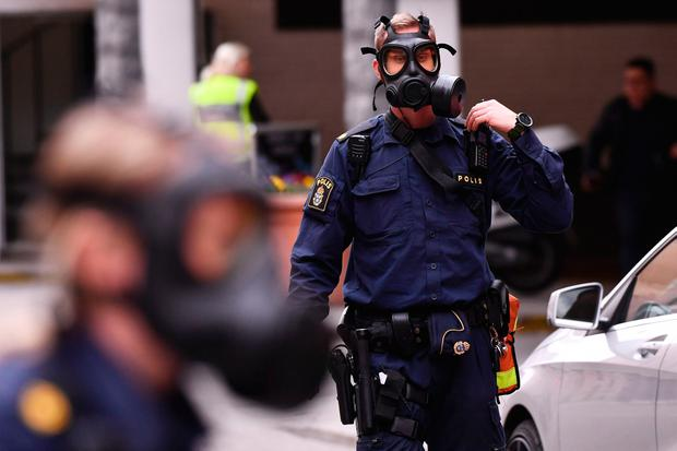 Police officers in gas masks work at the scene where a truck crashed into the Ahlens department store at Drottninggatan in central Stockholm, April 7, 2017. AFP/Getty Images