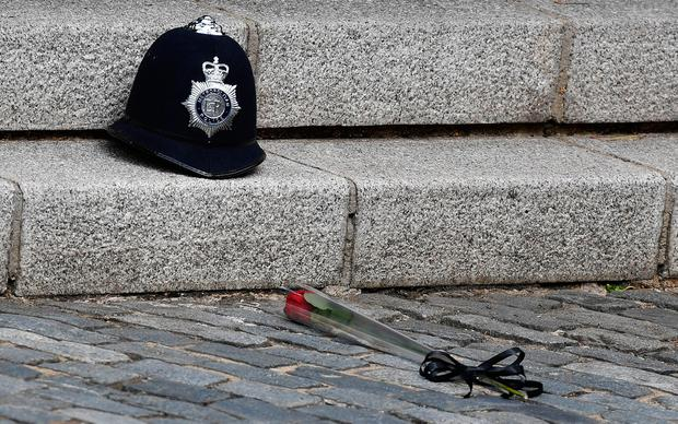 A single red rose is pictured in front of the police helmet of PC Keith Palmer, the officer killed in the March 22 Westminster terror attack, as the hearse carrying his coffin leaves the Chapel of St Mary Undercroft within the Palace of Westminster in central London, en route to Southwark Cathedral.