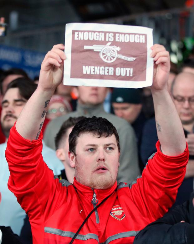 An Arsenal fan holds up a banner in protest against manager Arsene Wenger during the Premier League match at Selhurst Park, London. PA