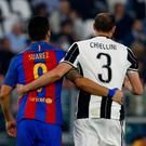 Barcelona's Uruguayan forward Luis Suarez (L) and Juventus' defender from Italy Giorgio Chiellini walk together during the UEFA Champions League quarter final first leg football match Juventus vs Barcelona, on April 11, 2017 at the Juventus stadium in Turin. AFP/Getty Images