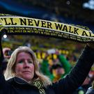 A fan holds up a scarf during the UEFA Champions League 1st leg quarter-final football match BVB Borussia Dortmund v Monaco in Dortmund, western Germany on April 12, 2017. AFP/Getty Images