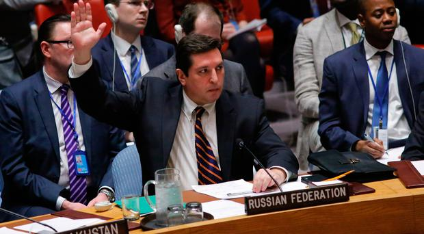 Russian Deputy Permanent Representative to the United Nations Vladimir Safronkov holds up his hand as he votes against a Draft resolution that condemns the reported use of chemical weapons in Syria at the Security Council on April 12, 2017 at UN Headquarters in New York. AFP/Getty Images