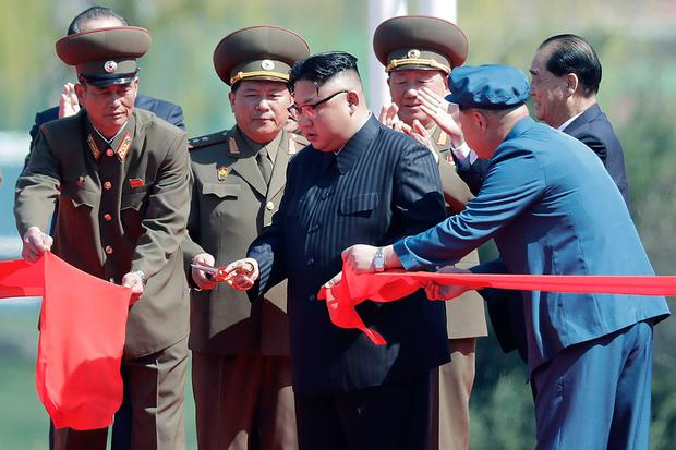 North Korean leader Kim Jong Un, center, stands with officials as he cuts the ribbon at the official opening of the Ryomyong high-rise district, Thursday, April 13, 2017, in Pyongyang, North Korea. (AP Photo/Wong Maye-E)