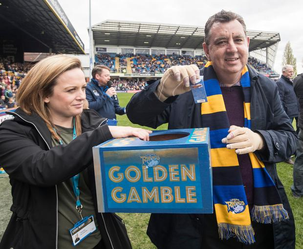 Chris King, the UK's first double hand transplant patient, holds up a Golden Gamble ticket after the Leeds Rhinos rugby league team ran onto the pitch at Headingley Carnegie stadium in Leeds ahead of their Super League match against Widnes Vikings. PA