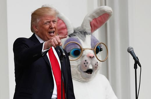 President Donald Trump (left), joined by the Easter Bunny (right), speaks from the Truman Balcony during the annual White House Easter Egg Roll, Monday, April,17, 2017, on the South Lawn of the White House in Washington. (AP Photo/Carolyn Kaster)