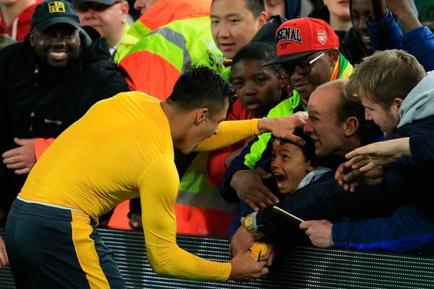 Arsenal's Chilean striker Alexis Sanchez gives his match shirt to a young fan following the English Premier League football match between Middlesbrough and Arsenal at Riverside Stadium in Middlesbrough, northeast England on April 17, 2017. AFP/Getty Images