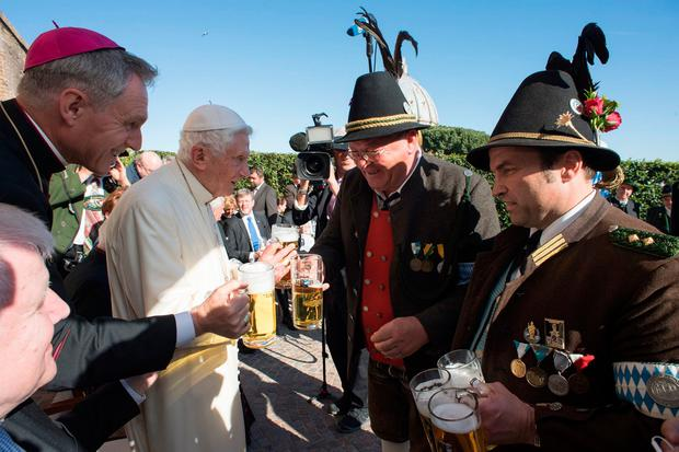 In this handout picture released by the Vatican Press Office Pope Emeritus Benedict VI (2ndL) drinks a glass of beer with Benedict's private secretary Georg Gaenswein (L) and a delegation from Bavaria during a party to celebrate his 90th birthday, on April 17, 2017 in Vatican's garden. / AFP PHOTO / OSSERVATORE ROMANO / HO / RESTRICTED TO EDITORIAL USE - MANDATORY CREDIT