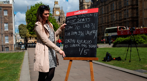 An employee with betting company Ladbrokes holds up betting odds on a blackboard in College Green outside the Houses of Parliament yesterday after Prime Minister Theresa May called a general election. Photo: Jack Taylor/Getty Images/