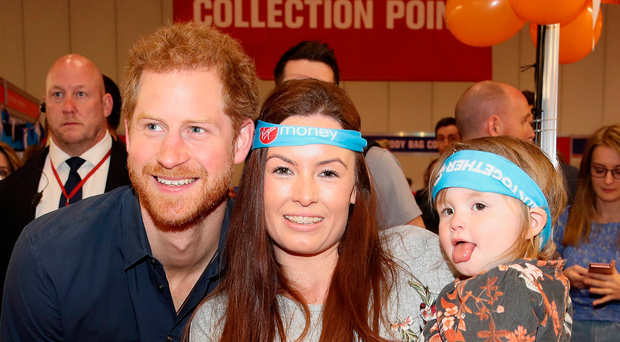 Prince Harry meets a mother and her young child as he officially opens the Virgin Money London Marathon Expo at ExCel in London