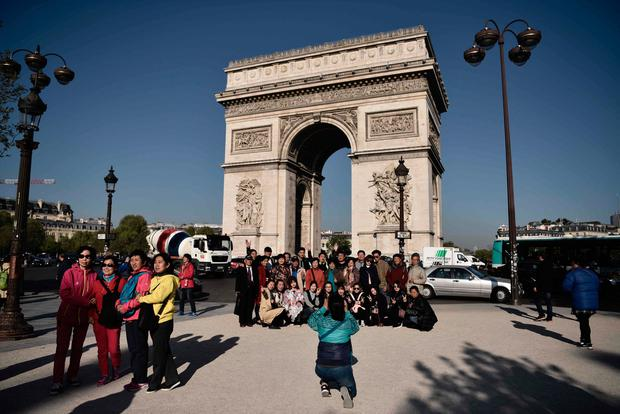 Tourists take pictures on the Champs Elysees avenue near the Arc de Triomphe monument in Paris on April 21 ,2017, a day after a gunman opened fire on police on the avenue, killing a policeman and wounding two others in an attack claimed by the Islamic State group just days before the first round of the presidential election. / AFP PHOTO / Philippe LOPEZPHILIPPE LOPEZ/AFP/Getty Images