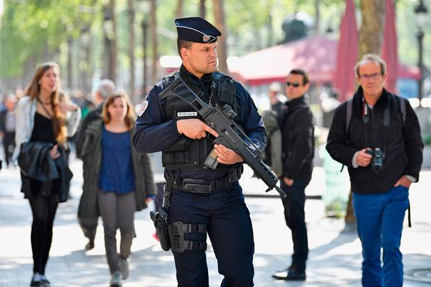 Armed police patrol the Champs Elysees in Paris following yesterday's shooting of a police officer on April 21 2017.