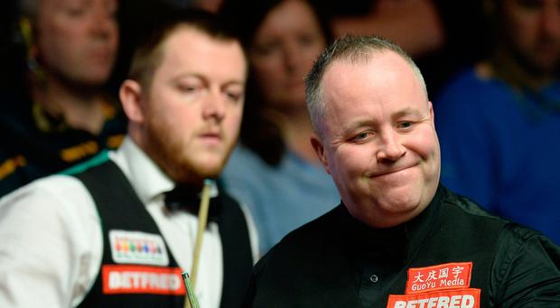 John Higgins (right) at the table in his match against Mark Allen on day seven of the Betfred Snooker World Championships at the Crucible Theatre, Sheffield.