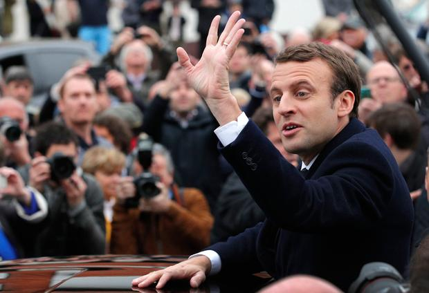 Centrist candidate Emmanuel Macron waves supporters after casting his vote in the first round of the French presidential election, in le Touquet, northern France, Sunday April 23, 2017. (AP Photo/Christophe Ena)