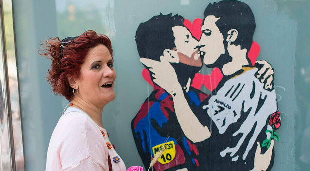 A woman holding a rose poses with the piece of street art titled Love is blind, depicting Barcelona's Lionel Messi and Real Madrid's Cristiano Ronaldo kissing by street artist Salva Tvboy, in Barcelona on April 23, 2017.