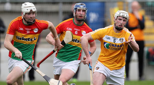 Making ground: Antrim's Paddy Burke in action against Martin Kavanagh and David English