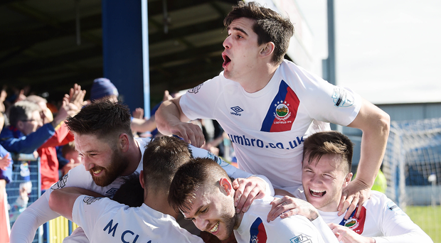 Title dream: Andy Waterworth is mobbed after scoring to help Linfield climb to the top of the table