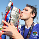 Sealed with a kiss: Noel Bailie plants a smacker on the Gibson Cup after his final game for Linfield