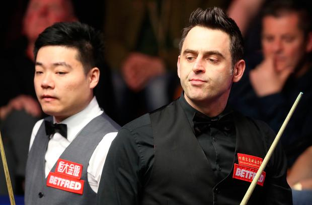 Ronnie O'Sullivan reacts after a shot during his match against Ding Junhui (left), on day twelve of the Betfred Snooker World Championships at the Crucible Theatre, Sheffield. PA