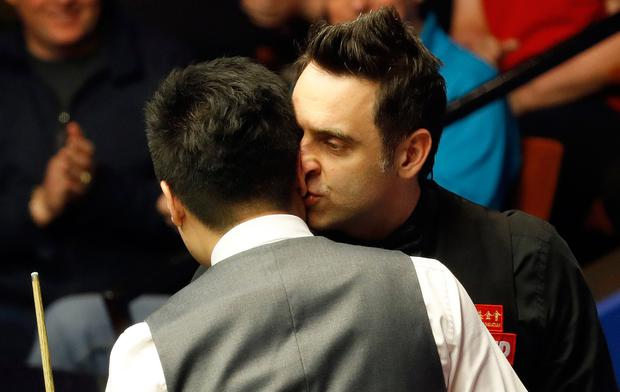Ronnie O'Sullivan (right) congratulates Ding Junhui on his quarter final win, on day twelve of the Betfred Snooker World Championships at the Crucible Theatre, Sheffield. PA