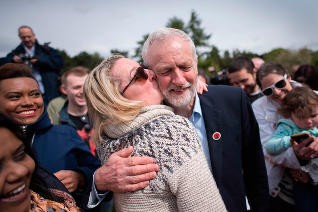 Labour leader Jeremy Corbyn is kissed by a supporter at a rally in Harlow, Essex. PA