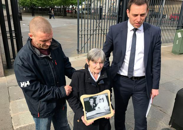 Teresa Watt, wife of Barney Watt, outside Belfast Coroner's Court with a photo of them on their wedding day, with her son Sean watt (left) and lawyer Padraig O' Muirigh (right). PA