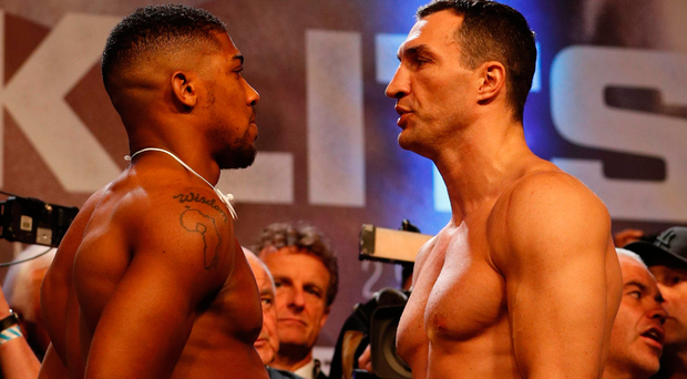 Facing off: Anthony Joshua and Wladimir Klitschko size each other up for the final time at yesterday's weigh-in
