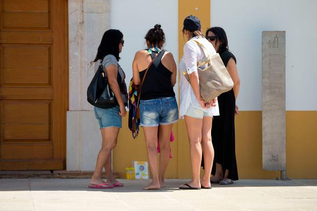 Tourists look at a tribute to Madeleine McCann is left outside the Church of Nossa Senhora da Luz in Praia Da Luz, Portugal, close to where Madeline McCann went missing from 10 years ago on May 3rd. PRESS ASSOCIATION Photo. Picture date: Wednesday May 3, 2017. Madeleine was three when she vanished from apartment 5A on Rua Dr Agostinho da Silva in the Algarve village at about 9pm on May 3 2007. See PA story POLICE Portugal. Photo credit should read: Steve Parsons/PA Wire