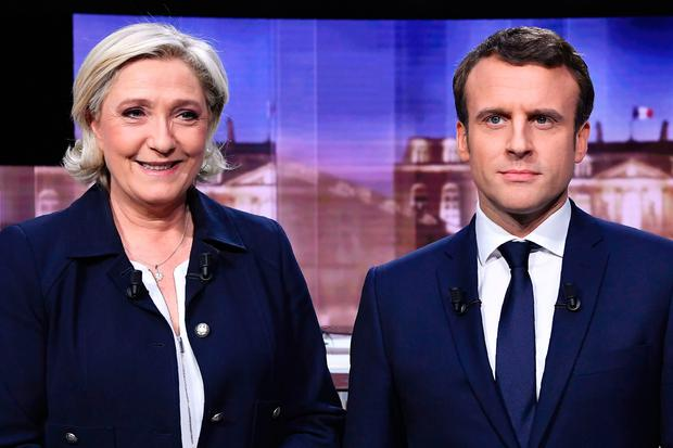 French presidential election candidate for the far-right Front National (FN) party, Marine Le Pen (left) and candidate for the En Marche ! movement, Emmanuel Macron pose prior to the start of a live brodcast face-to-face televised debate in television studios. AFP/Getty Images