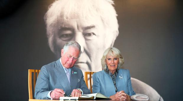 Prince Charles and Camilla, Duchess of Cornwall, adding their names to the guestbook at Homeplace, the centre dedicated to the works of poet Seamus Heaney