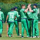 Well done: Craig Young is congratulated by Ireland Wolves captain Shane Getkate (right) after taking the wicket of Soumya Sarka