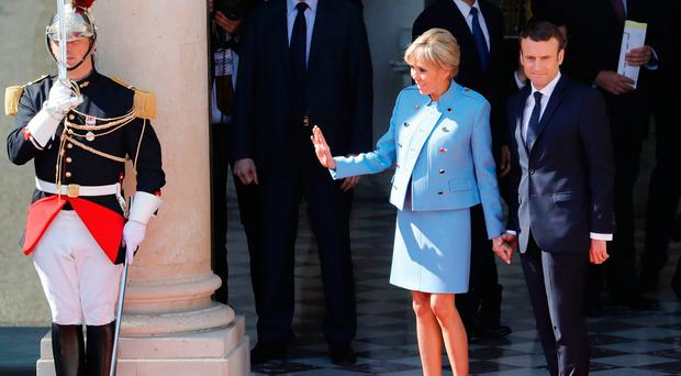 French newly elected President Emmanuel Macron (R) stands next to his wife with his wife Brigitte Trogneux at the Elysee presidential Palace before his formal inauguration ceremony on May 14, 2017 in Paris. / AFP PHOTO / POOL / Patrick KOVARIKPATRICK KOVARIK/AFP/Getty Images