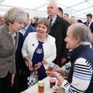 Elizabeth Warden of the Women's Institute introduces Theresa May to Lesley Martin and Dorothy Robb at the Balmoral Show