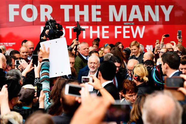 Crowd gathers round the leader of the Labour Party Jeremy Corbyn (C) as he attends a campaign rally in Beaumont Park after launching the Labour Party Election Manifesto on May 16, 2017 in Huddersfield, England. Britain will vote in a general election on June 8. (Photo by Leon Neal/Getty Images)