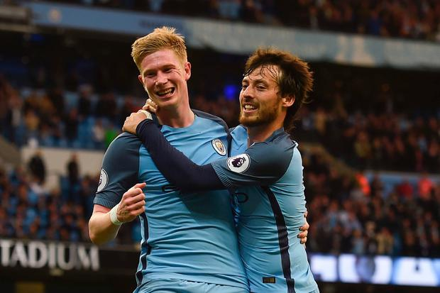 Manchester City's Belgian midfielder Kevin De Bruyne (L) celebrates scoring their second goal with Manchester City's Spanish midfielder David Silva (R) during the English Premier League football match between Manchester City and West Bromwich Albion at the Etihad Stadium in Manchester, north west England, on May 16, 2017. AFP/Getty Images