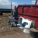 Sinn Fein South Down councillor Sean Doran with the destroyed and dumped posters at Kilkeel Harbour.