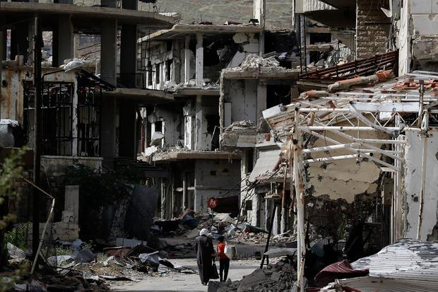 Residents walk through damaged streets at the mountain resort town of Zabadani in the Damascus countryside, Syria, Thursday, May 18, 2017. A U.S. airstrike struck pro-Syrian government forces for the first time, hitting a convoy in the desert near the border with Jordan, U.S. officials and Syrian activists said, an apparent signal to President Bashar Assad to keep his forces out of a zone where U.S.-backed rebels are fighting the Islamic State group. (AP Photo/Hassan Ammar)