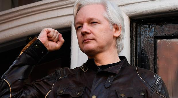 Wikileaks founder Julian Assange raises his fist prior to addressing the media on the balcony of the Embassy of Ecuador in London on May 19, 2017. AFP/Getty Images