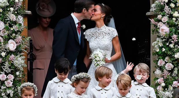 Pippa Middleton (R) kisses her new husband James Matthews, following their wedding ceremony at St Mark's Church in Englefield, west of London, on May 20, 2017, as the bridesmaids, including Britain's princess Charlotte (L) and pageboys, including Britain's prince George (2R), walk ahead. Justin TALLISJUSTIN TALLIS/AFP/Getty Images