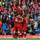 On course: Philippe Coutinho is mobbed after firing Liverpool 2-0 up