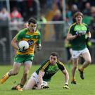 Grounded: Eoin McHugh leaves Antrim's Declan Lynch in his wake as Donegal coast to victory