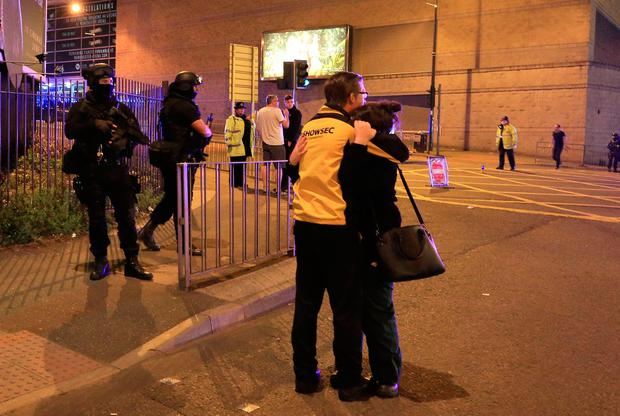 Armed police (left) at Manchester Arena after reports of an explosion at the venue during an Ariana Grande gig. Peter Byrne/PA Wire