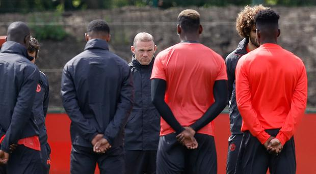 Manchester United's Wayne Rooney stands alongside team-mates for a minute silence in memory of the victims of the Manchester terror attack during the final training session at the AON Training Complex in Carrington, ahead of the Europa League Final against Ajax.